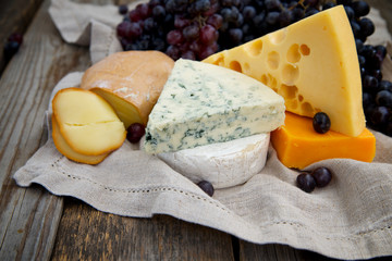 Set of cheeses with a bottle of red wine and dark grapes