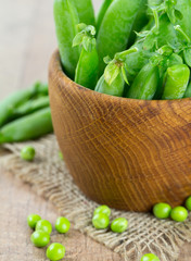 fresh pea pods in a wooden bowl