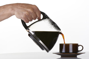man's hand holding and pouring coffee into a brown cup