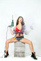Sexy young woman sits on a brick builder building tools near