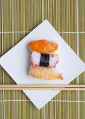 Sushi nigiri in with dish with bamboo sticks