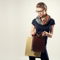 Young stylish female shopper looking into shopping bag