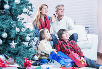 Family near Chrismas tree awaiting Santa Claus arrival