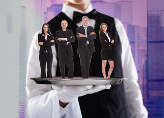 Business People On Silver Tray Being Carried By Waiter
