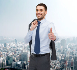smiling young businessman showing thumbs up