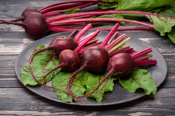 Raw beets with leaves on dark background