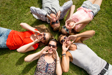 group of smiling friends lying on grass outdoors