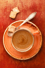 Cup of coffee and sugar on textured background