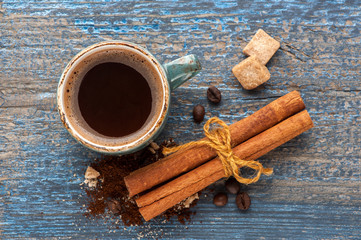 Cup of coffee and spices on vintage wooden background