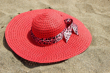 Women's hat, lying on the sand on the beach.