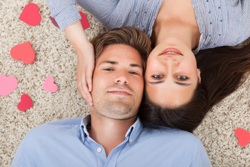 Loving Couple Lying On Rug At Home