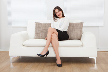 Beautiful Businesswoman Sitting On Sofa At Home