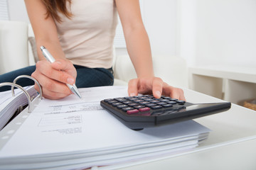 Woman Calculating Home Finances At Table