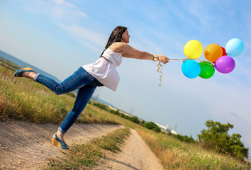 pregnant woman with bright colorful balloons