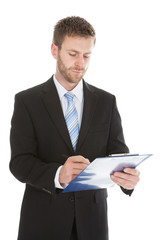Businessman Writing Notes On Clipboard