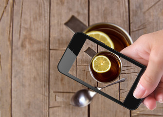 Hands taking photo cup tea with smartphone