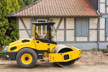 Ein gelber Walzenzug steht vor einem Fachwerkhaus