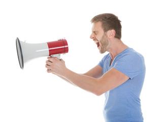 Full Length Of Man Screaming Into Megaphone