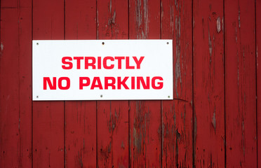 strictly no parking sign on red wood background texture