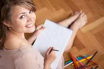 Pretty young woman  drawing for fun while sitting on the floor