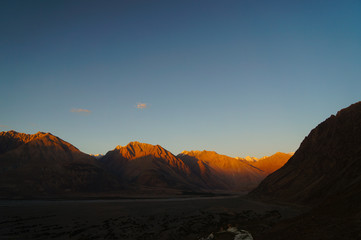 Sunset over Himalayas mountains in Nubra valley near  Diskit Gom