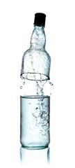 Fresh water splashing out of bottle, isolated on white backgroun