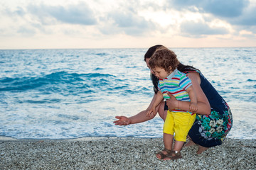 Mother and child collect pebbles on beach