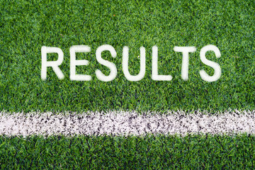 RESULTS hand writing text on soccer field grass