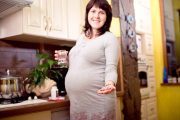 Young beautiful pregnant woman taking pills, vitamins, medicines