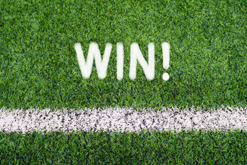 WIN hand writing text on soccer field grass