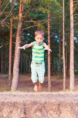 European boy jumping down the cliff forest
