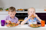 Happy little boy and girl eating Italian pizza