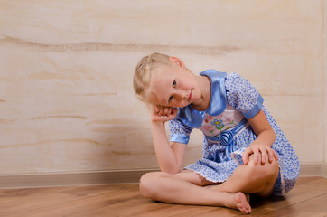 Cute young girl sitting in corner