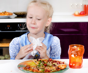 Pretty little girl eating homemade pizza