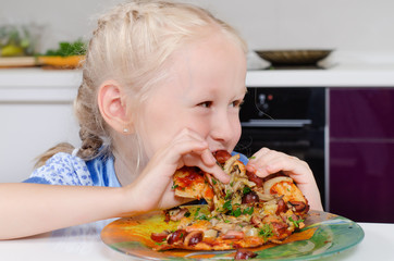 Happy young girl eating pizza