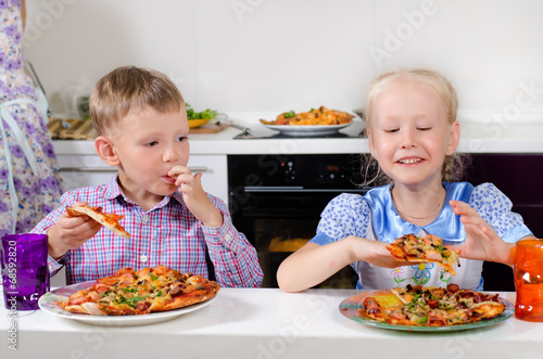 Happy little boy and girl eating Italian pizza