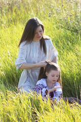 Mother daughter weaves a braid