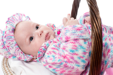 beautiful girl baby in a basket on a white background isolated