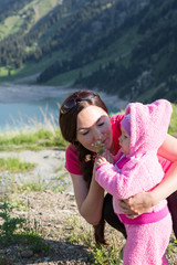 Happy mom and child girl hugging on nature