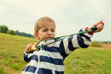 Маленький мальчик учится стрелять из рогатки