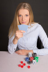 young attractive blond playing poker over grey