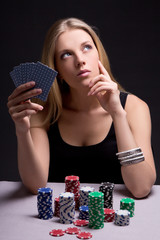 female poker player in casino with cards and chips