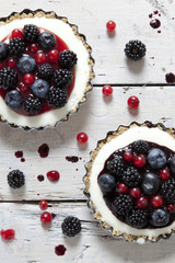 two cheesecake with blackberries blueberries and red currant