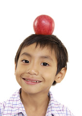 young boy with a red apple on the head
