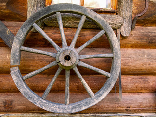 Hand spinning wheel on  wall of  old log house