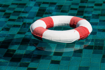 Life ring floating on top of sunny blue water
