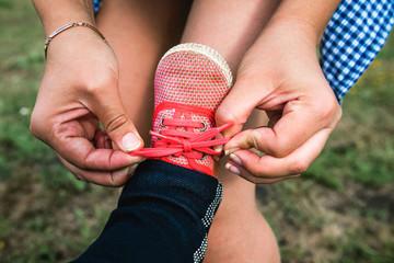 Мама завзыват шнурки на ботинках ребенка