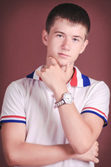 Handsome teenager in casual wear posing in studio. Stylish smili