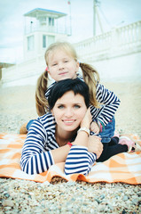 happy mother and adorable daughter on beach in cold season. beau