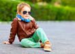 stylish boy in leather jacket posing on the ground